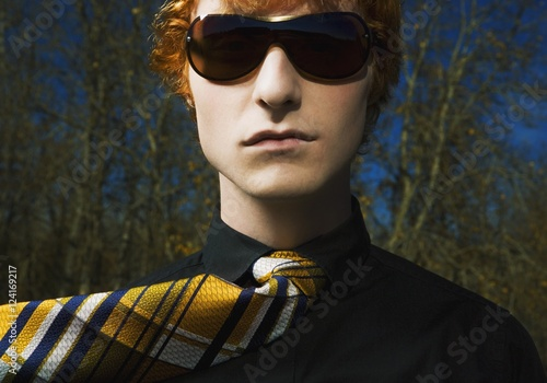 A Young Man Wearing Sunglasses And A Necktie