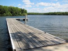 Wooden Dock Extends Into Blue Water Lake