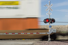 Railroad Crossing Sign And Passing Train. Photo Taken In The Mojave Desert Near Victorville In California.