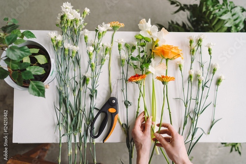 Foto op Canvas Bloemen Florist workspace: caucasian woman making floral decorations. Top view of flowers and greenery on white wooden table.