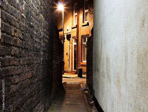 Looking down a dark empty back alleyway at night