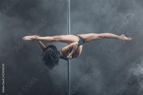 Fotografie, Obraz  Female pole dancer posing in dark studio