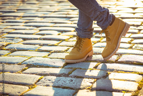Fotografía  Warm yellow boots. Walking in autumn leaves