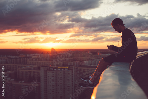 Young brave man sitting above the city with smartphone at sunset
