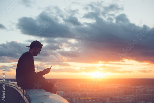 Fotografia  Risky man with smartphone chilling on the edge of the roof at sunset
