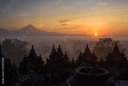Spoed Foto op Canvas Bali Die Stupas von Borobudur im Sonnenaufgang mit Vulkankegel im Hintergrund