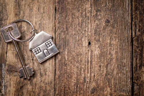 Photo House key on a house shaped keychain on wooden table