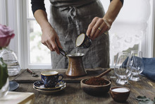 Woman Pouring Coffee Into Cup To Make Turkish Coffee