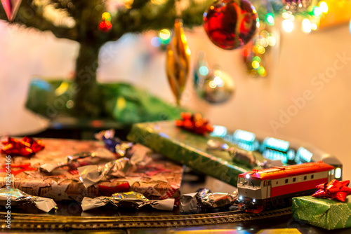 miniature train on table under christmas tree around gifts and candys - Train Under Christmas Tree