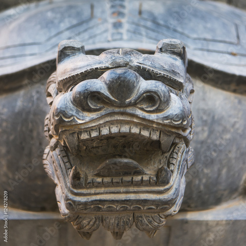Close up of the head of a carved stone animal looking fierce showing teeth Poster