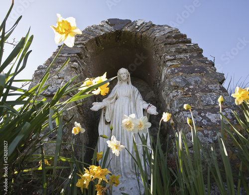 Papiers peints Con. ancienne A religious statue inside an arch stone structure and daffodils growing outside