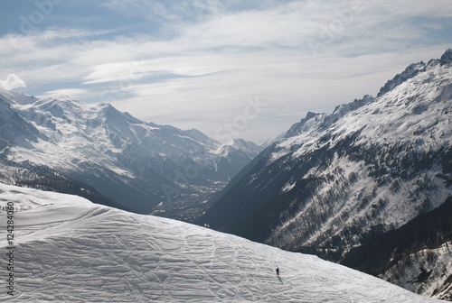 A person walks across a snow plateau with a view of the french alps;Chamonix-mont-blanc rhone-alpes france