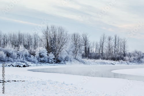 Fotobehang Landschap Frost and fresh snow cover the landscape and trees and the river is completely frozen with steam rising in the morning sun; Fort McMurray, Alberta, Canada