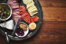 A Plate Of Sliced Cheeses And Meats