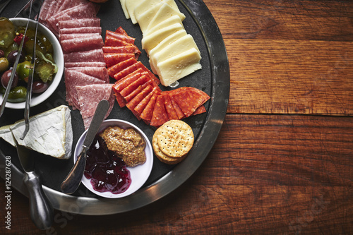 Photo Stands Assortment a plate of sliced cheeses and meats