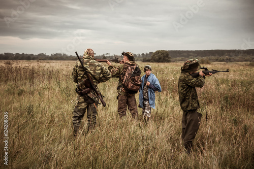 Fotobehang Jacht Hunting scene with hunters aiming during hunting season in rural field in overcast day with moody sky