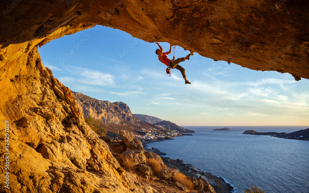 Fototapety, obrazy: Male climber on overhanging rock against beautiful view of coast below