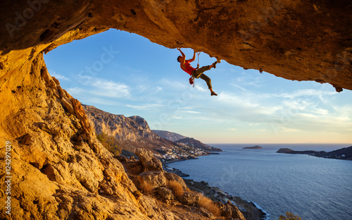 Male climber on overhanging rock against beautiful view of coast below Canvas Print