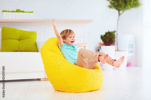 Fotografia  excited kid having fun, sitting on yellow bean bag at home