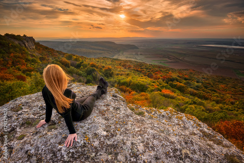 Sunset from the top / A woman on the top of a rock enjoys the view of sunset ov Canvas-taulu