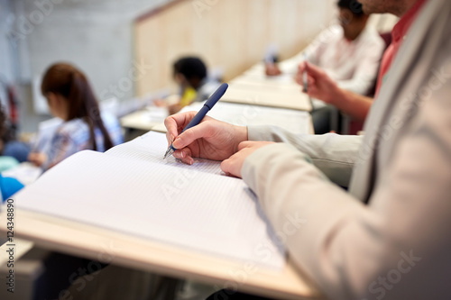 Fotografie, Obraz  student writing to notebook at exam or lecture