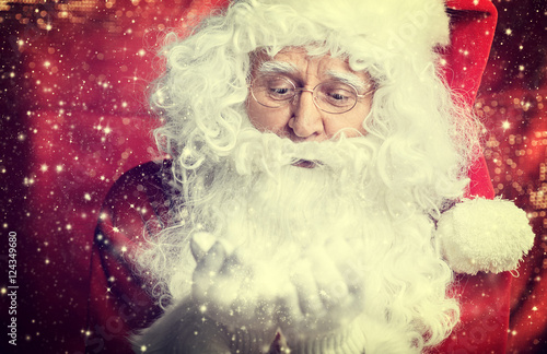 Image of Santa Claus in red costume against dark background