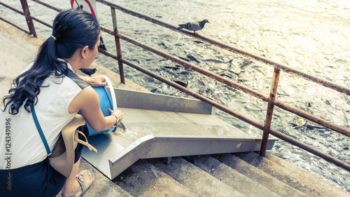 Woman Releasing Fish To The Chao Phraya River According To The
