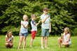kids with smartphones playing game in summer park