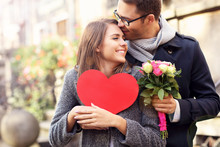 Young Couple With Flowers And Heart