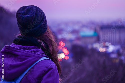 Girl looking at winter evening cityscape, purple violet sky and - 124377872