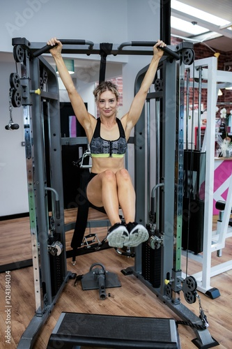 Woman performing stretching exercise with pull up bar