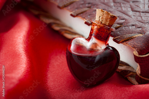 Photo Love potion leaning on a book of magic spells for Valentine's day