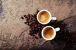 Two cups of coffee with coffee beans on a stone background