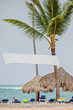 Empty tag ready for your text or sign. Sea view, palm trees, sun umbrellas, loungers and beach background.