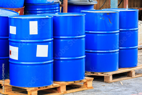Many blue barrels on wooden pallets
