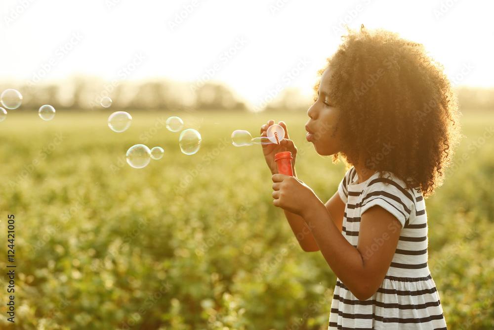 Fototapety, obrazy: Little African American girl blowing bubbles in field