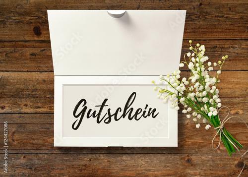 Gutschein - Text in Box mit Maiglöckchen auf rustikalem Holztisch Canvas-taulu