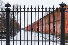 Wrought Iron Fence At The Background Of The Frozen Canal And Brick Facade Of Abandoned Building In Winter Scene.
