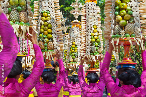 Foto op Plexiglas Indonesië Procession of beautiful Balinese women in traditional costumes - sarong, carry offering on heads for Hindu ceremony. Arts festival, culture of Bali island and Indonesia people. Asian travel background