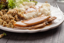 Oven Roasted Turkey Thanksgiving Platter With Mashed Potatoes, Gravy, Salad, And Stuffing Side View