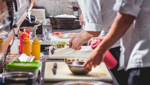 Fotografía  male cooks preparing sushi in restaurant kitchen