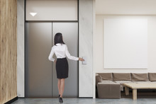 Woman Waiting For Elevator In Company Lobby