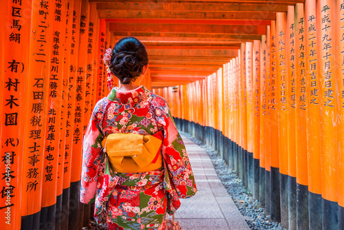 Poster Kyoto Women in kimono stand at Red Torii gates in Fushimi Inari shrine, one of famous landmarks in Kyoto, Japan