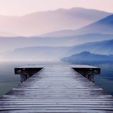wooden pier on lake site facing a beautiful mountain on a misty winter morning - 124500655