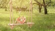 Flowers on wooden swing under blossoming apple trees, sun flare