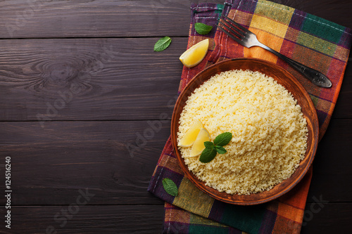 Couscous with mint and lemon in plate on dark rustic table from above. Copy space for text.