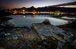 Long exposure in the gulf of Elounda village at night with foreground a stoned water tank.