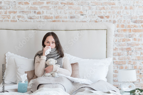 Fotografia  Unhappy sick woman resting on the bed