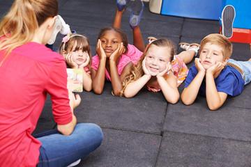Fototapeta samoprzylepna Children listening to story from book in kindergarten