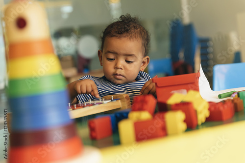 Photo  Happy baby playing with toy blocks.